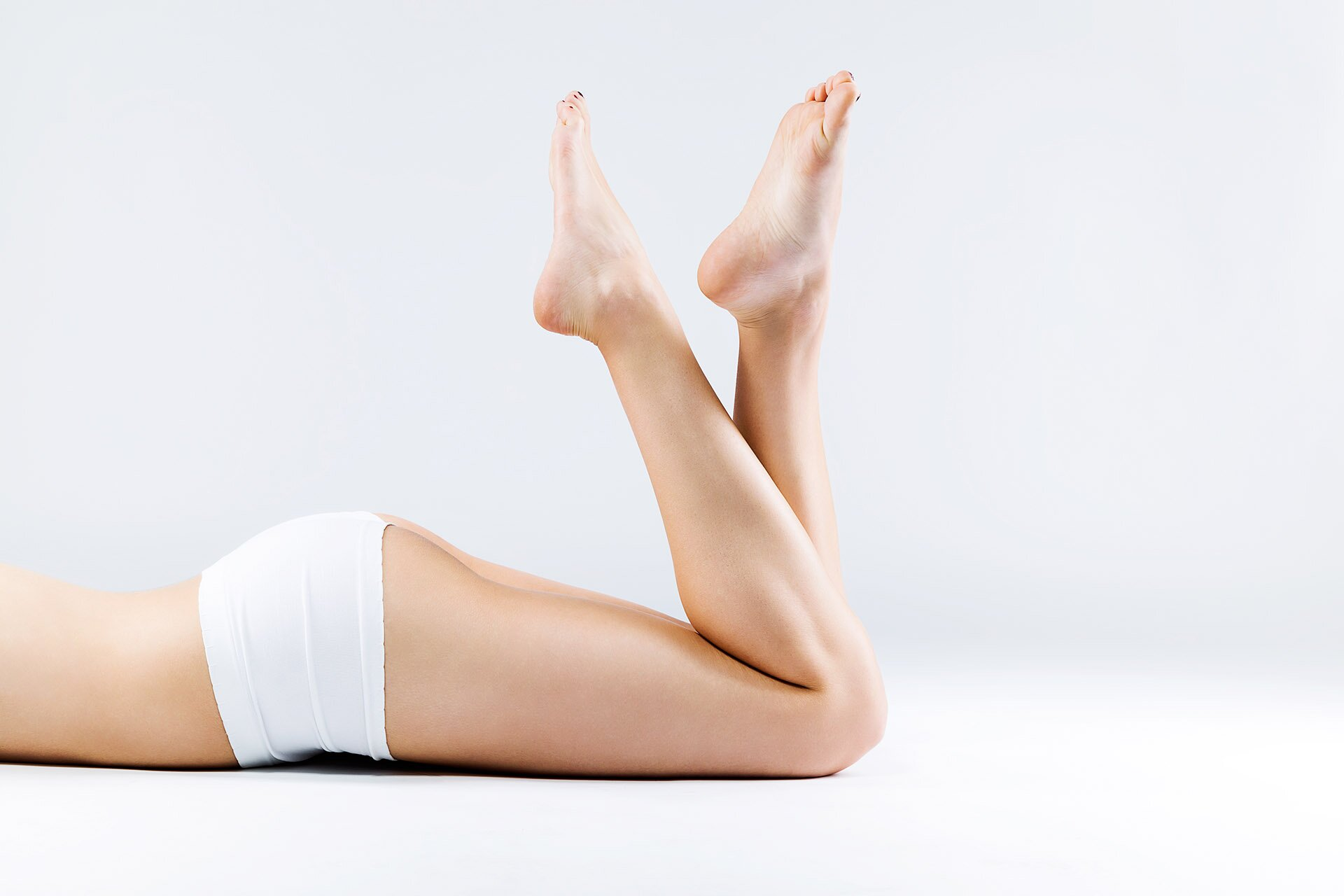 Perfect smooth and waxed woman legs with feet pointing up.