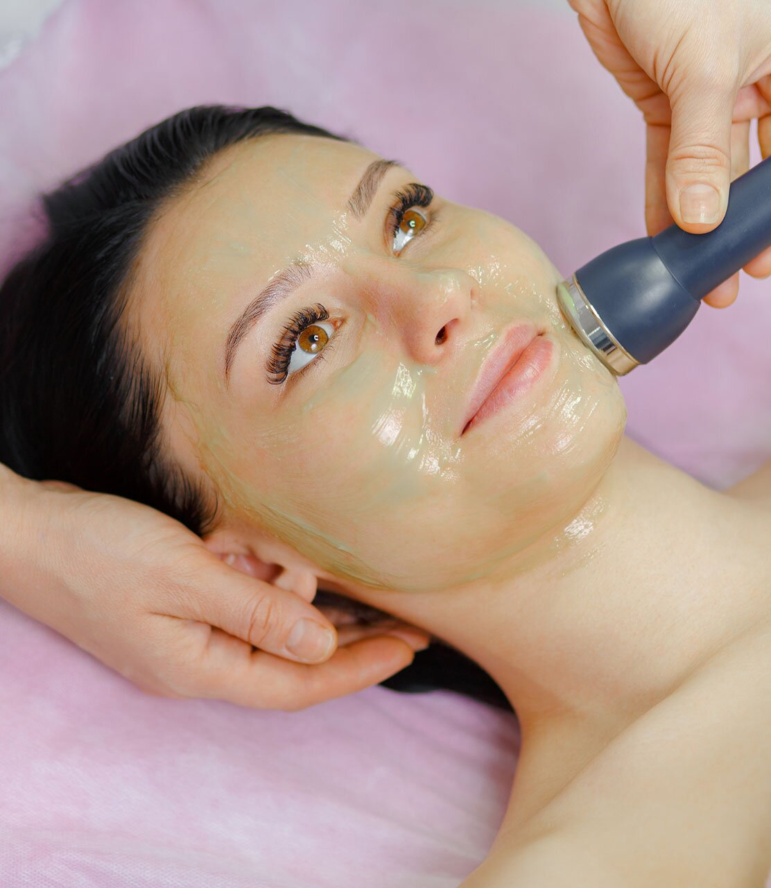 Young beautiful woman with dark hair gets procedure in the beauty salon